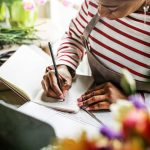 Business owner writing content ideas for her website in a notebook
