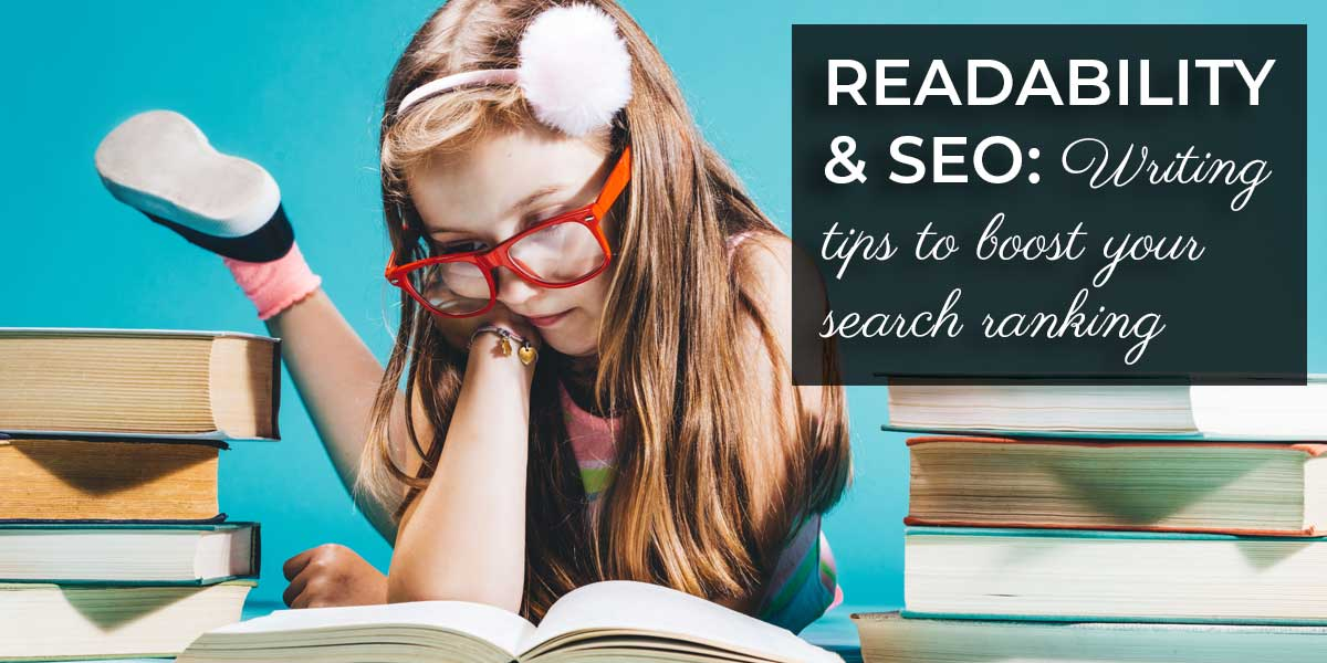 Little girl with read glasses reading a book with piles of books on either side